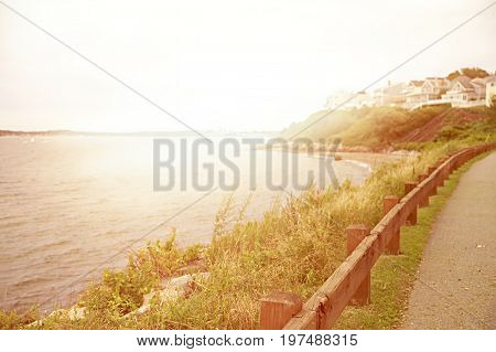 Sea shore with the city in the distance. Wooden fence on the waterfront. blurred background. Copy space for your text