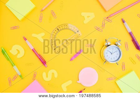 back to school or office styed pattern with multicolored school supplies on yellow