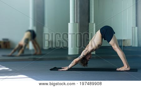 Handsome Tattooed Man Practicing Yoga. Young Male Teacher Taking Downward Facing Dog Pose, Adho Mukh