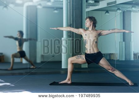 Handsome Tattooed Man Practicing Yoga. Young Male Teacher Taking Warrior Pose, Virabhadrasana Asana