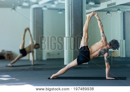 Handsome Tattooed Man Practicing Yoga. Young Male Teacher Taking Side Plank Pose, Vasisthasana Advan