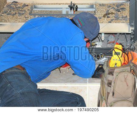 JANUARY 24, 2017. SEATTLE, WA. CIRCA: Maintenance man doing repairs on a broken fireplace inside a home.