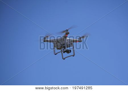 White drone equipped with video camera hovering in mid air. Flying drone with camera