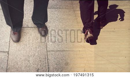 Concepts of continue or quit; stay or walk away; stop or go. Man is standing and walking away; taken from knees down; wearing black trousers and brown shoes. Retro style. Bottom copy space for text.