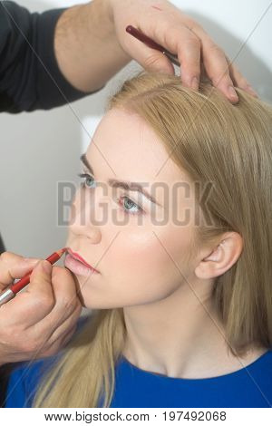 Visagiste Applying Red Pencil On Woman Lips