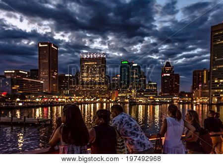 Baltimore Maryland USA - July 8 2017: Tourists view the illuminated Inner Harbor skyline on the City Light Cruise.