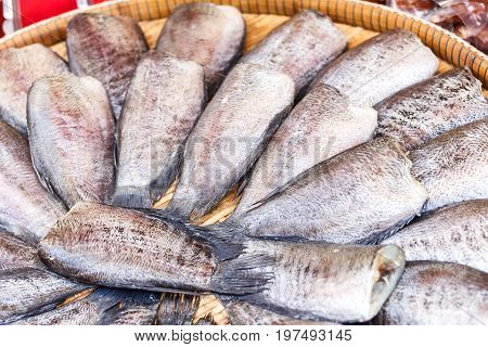 Dried salted snake skin gourami fish on bamboo weave wood in market for cooking.