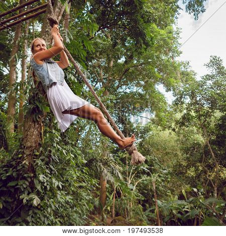 Family travel lifestyle. Happy young woman flying high with fun on rope swing on wild jungle background. Funny adventure walk in tropical rainforest. Leisure activity on summer vacation with kids.