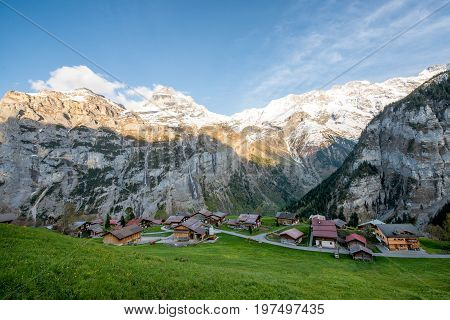 Farmhouse in village with swiss alps snow mountain in background in Grindelwald Switzerland. Country village in Switzerland.