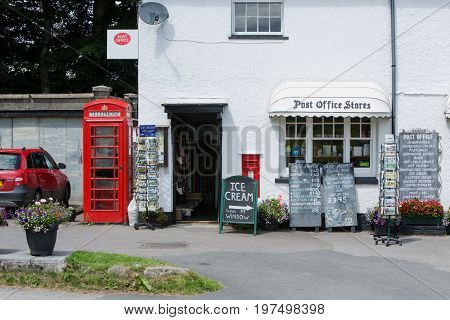 An old traditional post office store with a red telephone box and various advertising boards in the middle of the countryside in Dartmoor National Park Devon England 2017