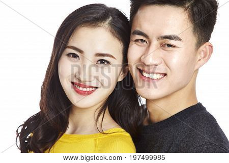 studio portrait of young asian couple looking at camera smiling head shot isolated on white background.