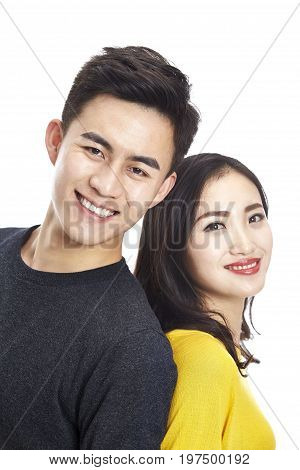 studio portrait of young asian couple standing back to back looking at camera smiling head shot isolated on white background.