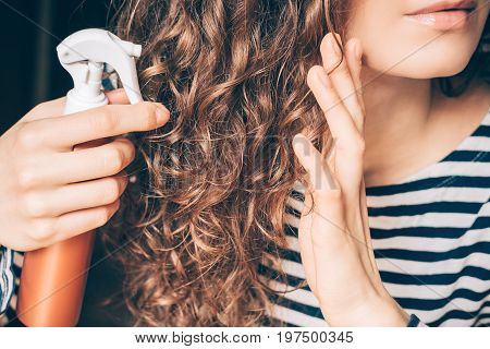 Woman Applying Spray On Curly Brown Hair