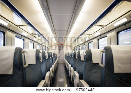 Empty interior of a passenger train car aka coach or carriage . Rows of unoccupied seats and folding tables in economy or second class. Public transport.