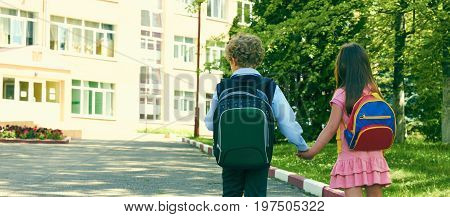 Back view of two pupils of primary school go hand in hand. Boy and girl with school bags behind the back. Beginning of school lessons.