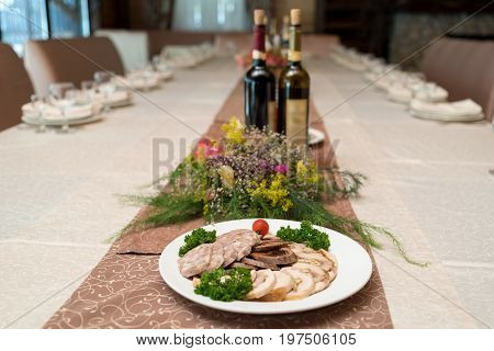 White plate with delicious sliced ham meatloaf tomato and parsley on celebratory dinner table in blur selective focus. Meat platter with selection