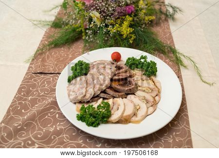 Cold meat plate with delicious sliced ham meatloaf tomato and parsley on celebratory dinner table selective focus. Meat platter with selection
