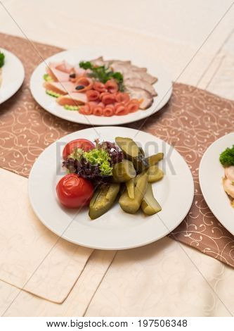 White Plate With Homemade Pickled Tomatoes, Cucumbers And Lettuce On Celebratory Dinner Table. Diffe