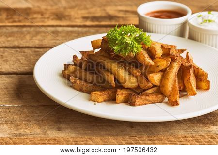 Homemade french fries serve with ketchup and sour cream or mayonnaise. Golden brown crispy french fries sprinkle with salt and oregano on white plate for snack or appetizer.French fries on wood table. Delicious french fries ready to served.