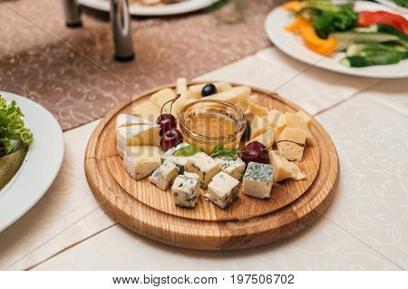 Cheese Plate With Cherries And Honey On Round Wooden Board Plate On Celebratory Dinner Table, Select