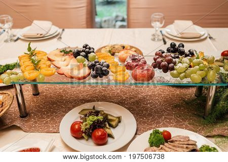 Fresh Grapes, Nectarine, Peach And Apricot With Sugar Powder On Glass Stand. Fruit Plate For Dessert