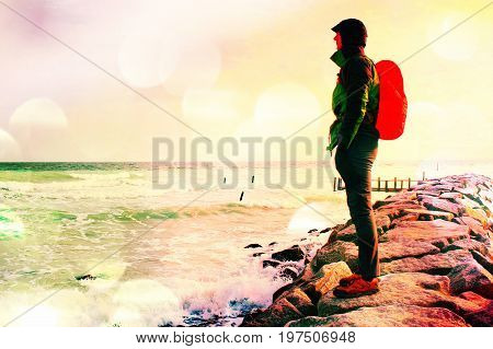 Film Grain. Tall Hiker In Dark Sportswear With Sporty Backpack In Raincoat  On Beach,  Horizon With