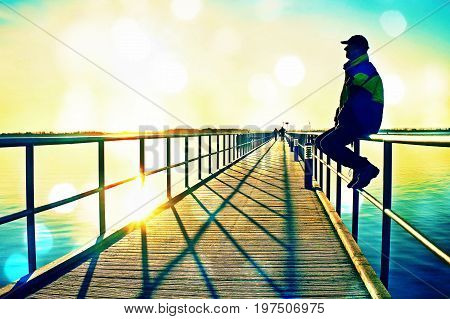 Film Grain. Man In Warm Jacket And Baseball Cap Sit On Pier Handrail Construction And Enjoy Morning