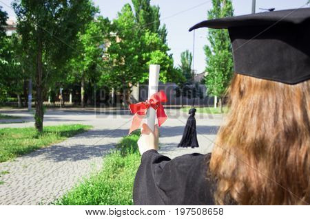 Graduate put her hands up and celebrating with certificate in her hand and feeling so happiness in Commencement day