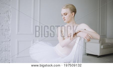 Beautiful ballerina with blonde hair is sitting on the chair in the classroom. Girl is crossing her arms and hanging them over the back of the chair. She is very serious and looking down to the floor. Close up