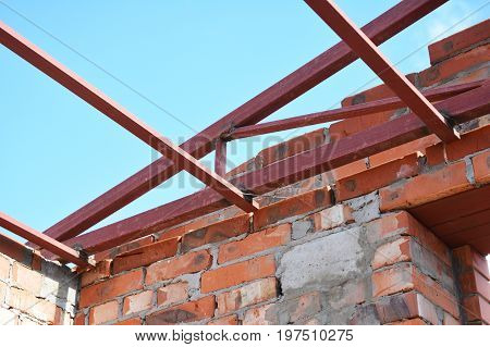 Steel roof trusses corner details. Roofing Construction. Steel roof trusses sitting on concrete pole view from inside.