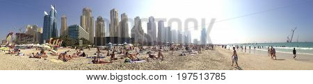 Dubai UAE - January 1 2015: People enjoy a sunbath at the luxurious Hilton Jumeirah Beach resort on the coast of the Persian Gulf. Panoramic view.