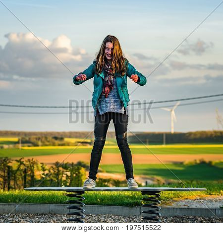 Teenage Girl Playing On Children Playground, Evening