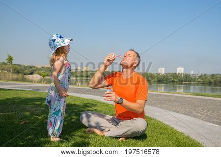 Father And His Little Daughter Intently Inflate Soap Bubbles