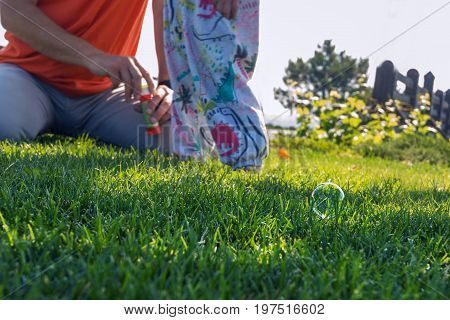 Soap bubble lies on the fresh green grass next to the feet of the father and little daughter who play with soap bubbles. Sunny morning in a park.
