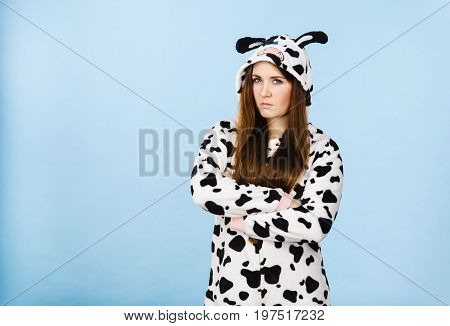 Teen girl in funny nightclothes pajamas cartoon style showing angry offended face expression studio shot on blue. Negative emotion concept.