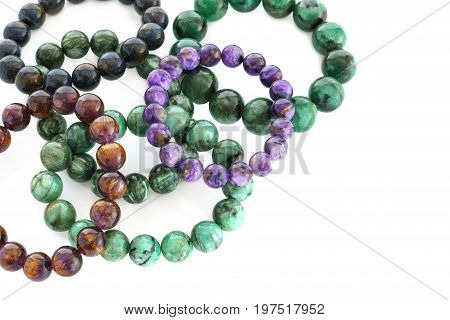 Close up Charoid Seraphinite Cacoxenite Pietersite and Emerald beads in bracelets on white background
