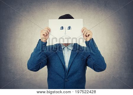 Businessman covering his face using a white paper with drawn sad emoticon sketch like a fake mask for hiding his real emotion from society. Isolated gray wall background.