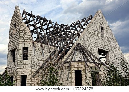 Part of the construction of a house of white brick and a roof with a wooden beam