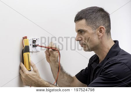 HVAC tech checking low voltage on a thermostat