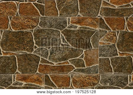 Brownish gray stone texture from a fragment of the basement with large cobblestones