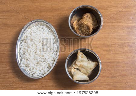 Rice, samosas and onion bhaji on a wooden background