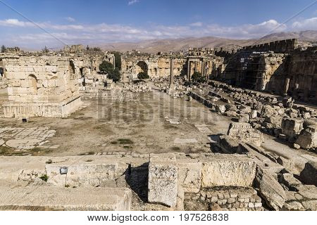 Ruins of Jupiter temple and great court of Heliopolis with mountains in the background in Baalbek, Bekaa valley Lebanon
