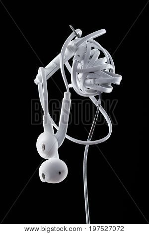 Earphone on fork on black background. Concept of Music