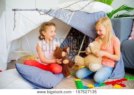 Two girls playing together in a wigwam in a living room
