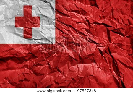 Tonga flag painted on crumpled paper background