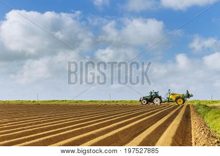 Plowed agricultural fields prepared for planting crops in Normandy, France. Countryside landscape with cloudy sky, farmlands in spring. Environment friendly farming and industrial agriculture concept