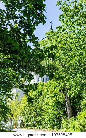 Montreal Canada - May 28 2017: St Joseph's Oratory on Mont Royal with dome framed by green trees during bright sunny day in Quebec region city