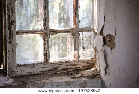 Old window with shabby cracked paint In the old forgotten house