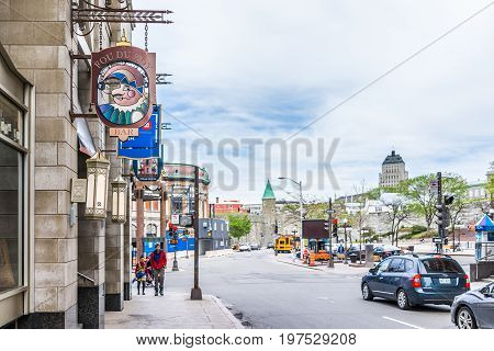 Quebec City Canada - May 29 2017: Old town street with sign for Fou du Roy restaurants St John's Gate and Chateau Frontenac