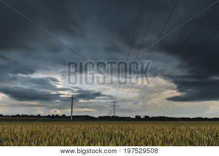 High Voltage Power Lines, Transmission Towers And Wind Turbines In Agricultural Fields On A Cloudy D